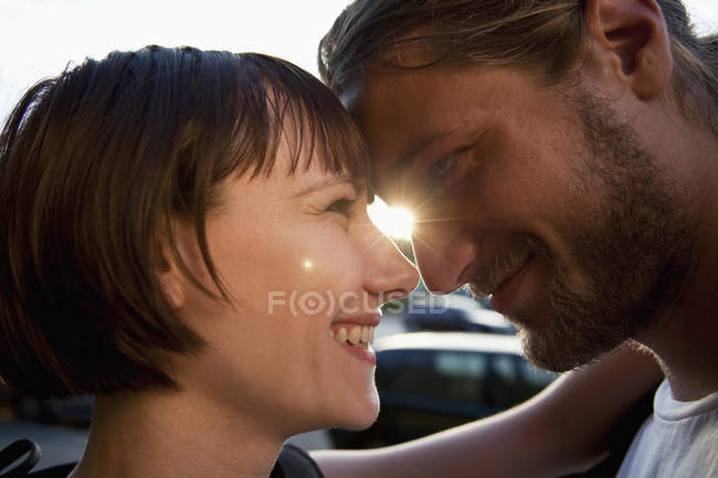 Close-up of loving young couple face to face in backlit — Stock Photo