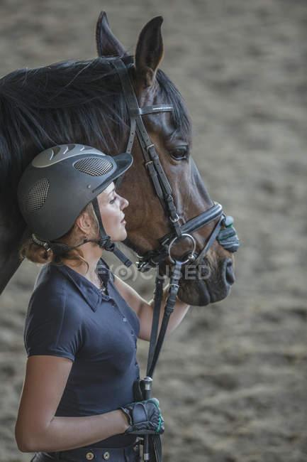 Vue de côté de femme avec cheval au testing — Photo de stock
