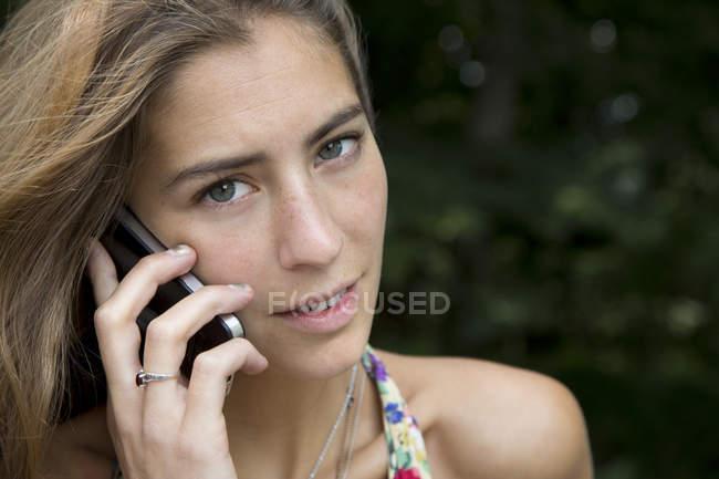 Primer plano de la mujer joven hablando por teléfono móvil - foto de stock