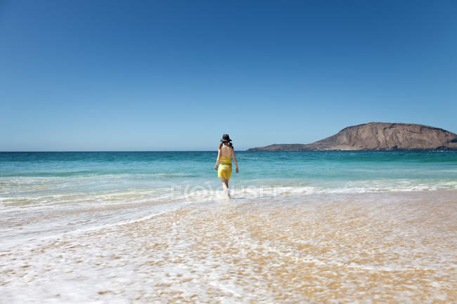 Rear view of woman walking through water on tropical beach — Stock Photo