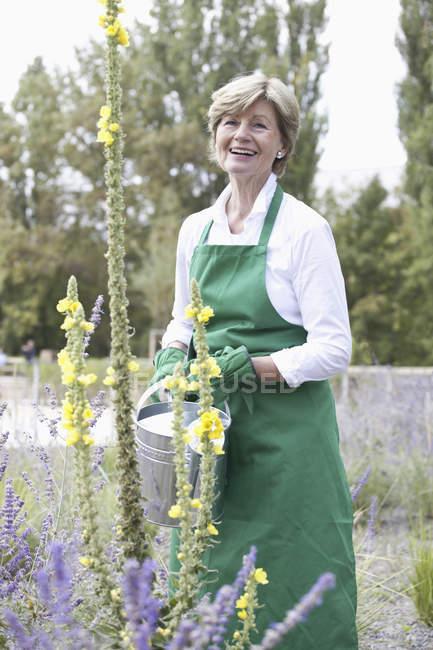 Усміхаючись Холдинг Літня жінка лійка в саду — стокове фото