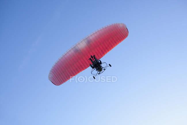 Visão de baixo ângulo do motor da pessoa parapente contra o céu claro — Fotografia de Stock