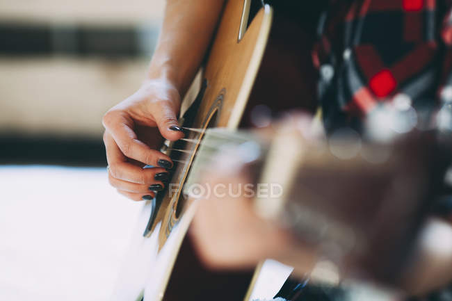 Recortar imagen de mujer tocando la guitarra en casa - foto de stock