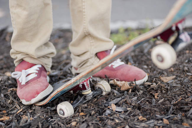 Low section of man with skateboard outdoors — Stock Photo