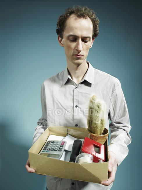Uomo che trasporta una scatola di beni dopo essere stato licenziato — Foto stock