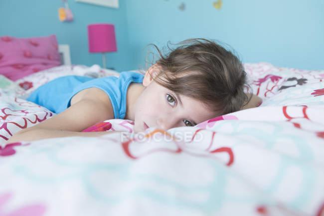 Retrato de menina cansada, deitada na cama em casa — Fotografia de Stock
