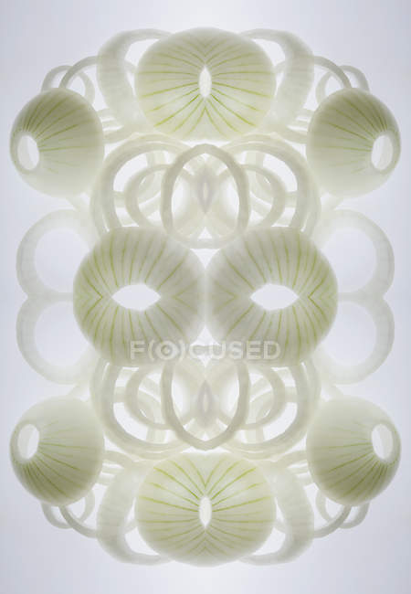 Digital composite of mirrored arrangement of onion rings — Stock Photo