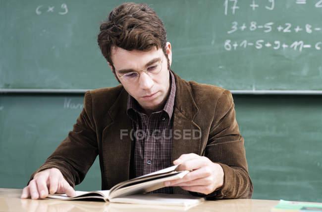 Шкільний учитель, читаючи книгу в класі — стокове фото