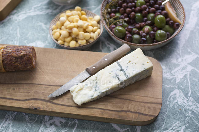 Close up view of cheese slice with olives and sweetcorns on table — Stock Photo