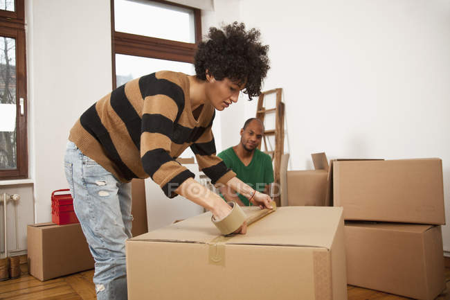 Woman taping moving box while man watching on background — Stock Photo