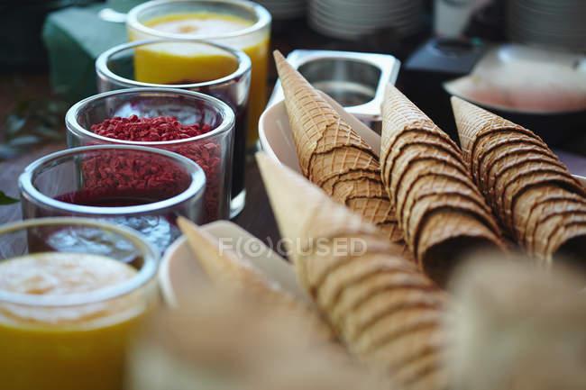Vista da vicino di coni gelato e vari sciroppi aromatizzati al negozio — Foto stock