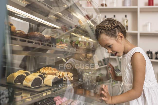 Vista lateral da garota admirando a sobremesa na loja de padaria — Fotografia de Stock
