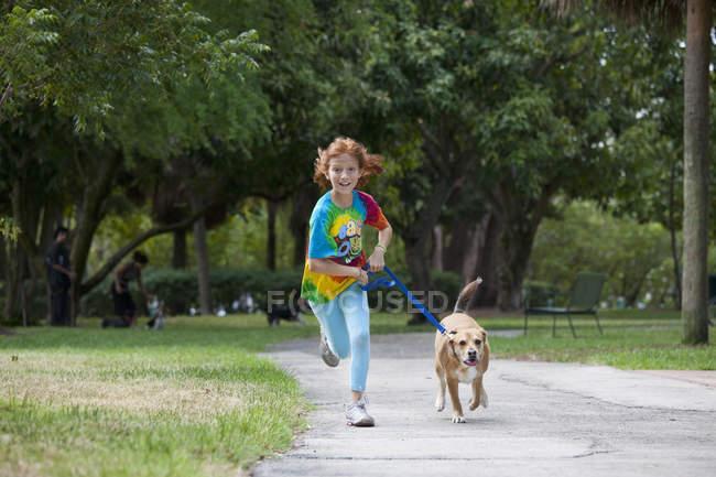 Ragazza che corre con il cane attraverso il parco — Foto stock