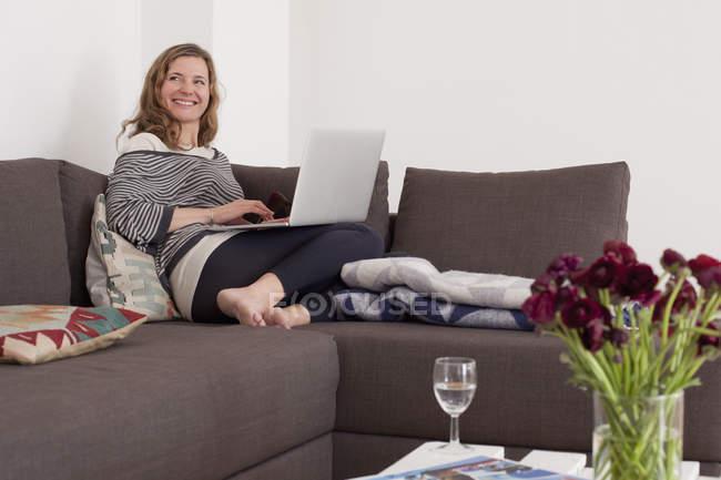Счастливая женщина смотрит в сторону, используя ноутбук на диване — стоковое фото