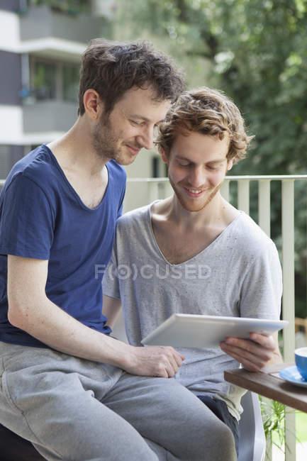 Gay couple using digital tablet at porch — Stock Photo