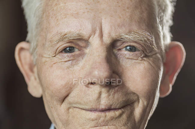 Close-up portrait of smiling senior man over colored background — Stock Photo