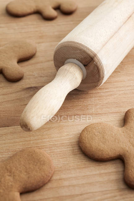 Unfrosted gingerbread men on wood table with rolling pin, close-up — Stock Photo