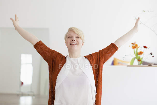 Smiling woman with arms outstretched standing at home — Stock Photo