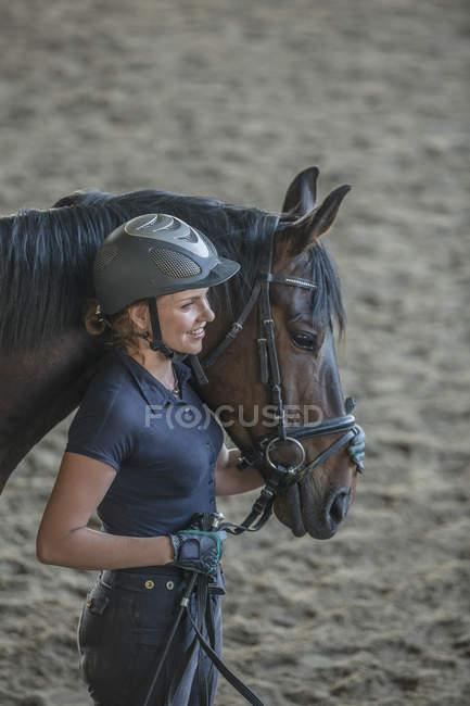Vue latérale d'une femme aimante avec cheval au testing — Photo de stock