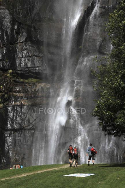 Vista posterior de los excursionistas a pie hacia la cascada - foto de stock