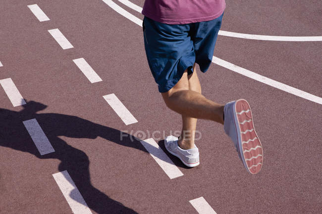 Low section of man jogging on track — Stock Photo