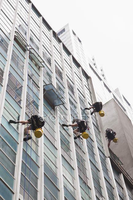 Vue à angle bas des travailleurs nettoyant les vitres du gratte-ciel — Photo de stock
