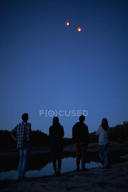 Задній вид друзі, дивлячись на папері ліхтарями політ в чисте синє небо — стокове фото