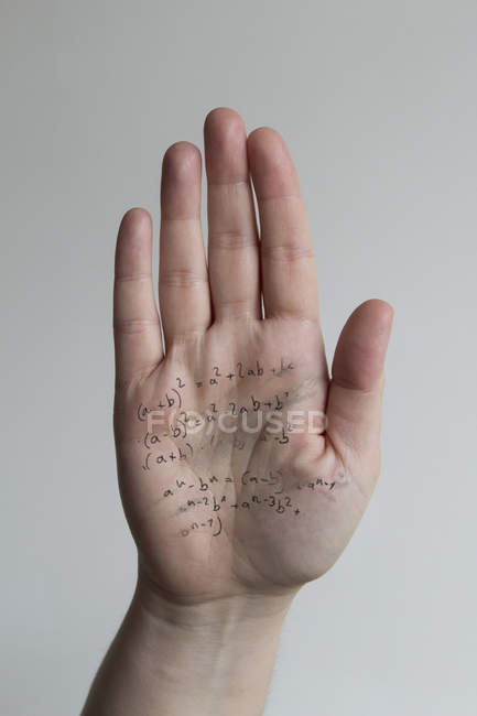 Crop male hand with written formulas against gray background — Stock Photo