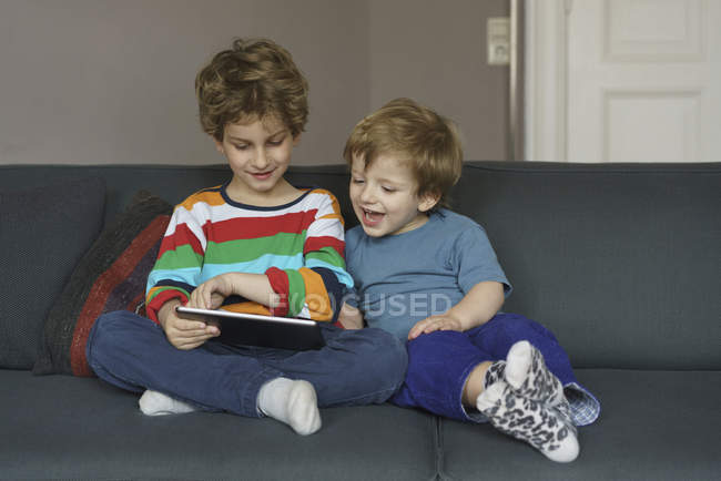 Happy siblings looking at digital tablet while sitting on sofa at home — Stock Photo