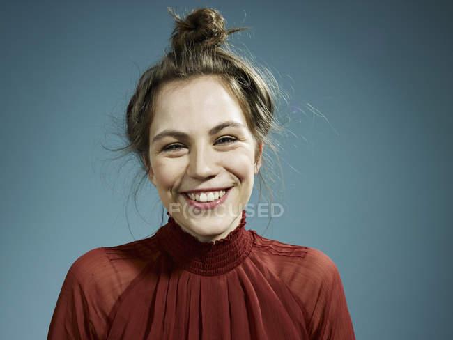 Retrato de la joven feliz sobre fondo azul - foto de stock