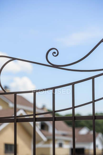 Gros plan de la barrière métallique contre les façades du bâtiment et le ciel bleu — Photo de stock
