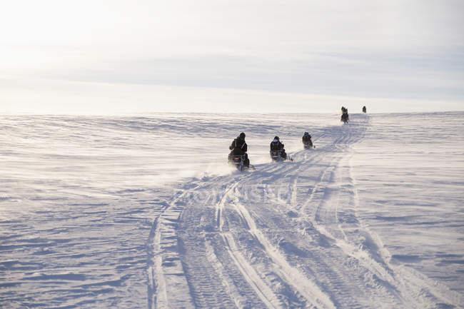 Vista traseira de pessoas dirigindo snowmobiles em campo contra o céu — Fotografia de Stock