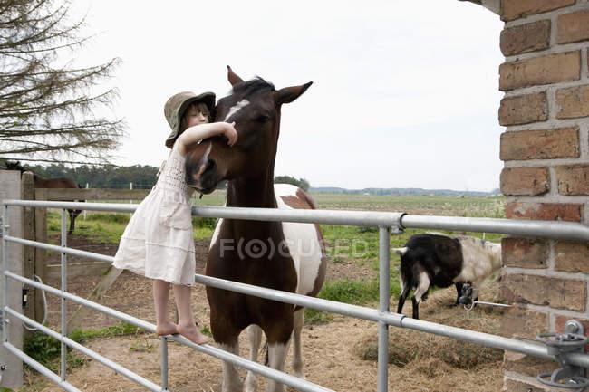 Jeune fille embrassant le cheval en se tenant debout sur la rampe à la ferme — Photo de stock