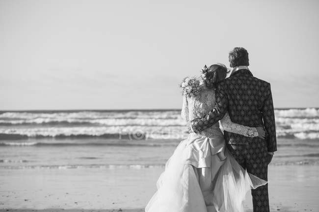Rear view of bride and groom standing arm around at beach — Stock Photo