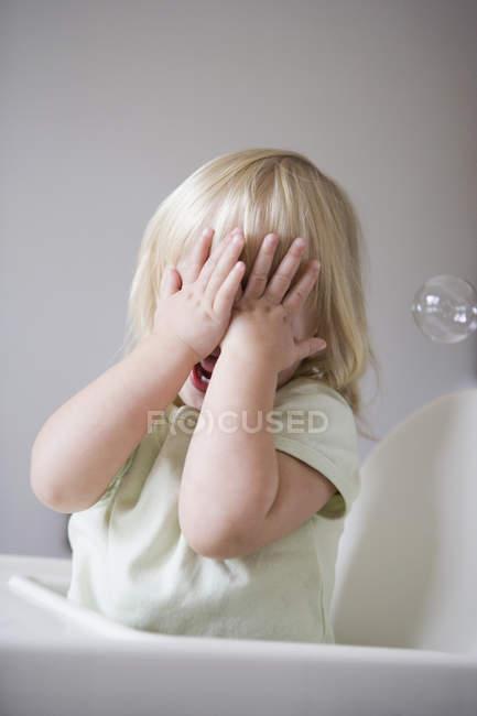 Молода дівчина, що охоплюють її обличчя з її рук — стокове фото