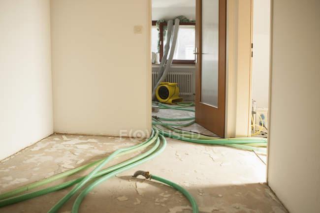 Зеленые шланги на полу в помещении под ремонт — стоковое фото