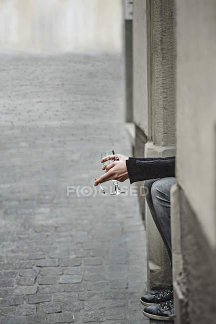 Imagen recortada de mujer sosteniendo cigarrillo y vino por acera - foto de stock
