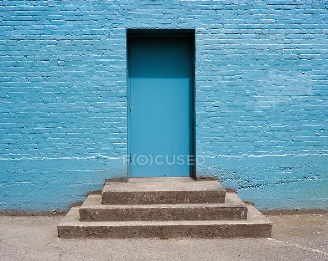 Concrete steps leading to blue doorway — Stock Photo