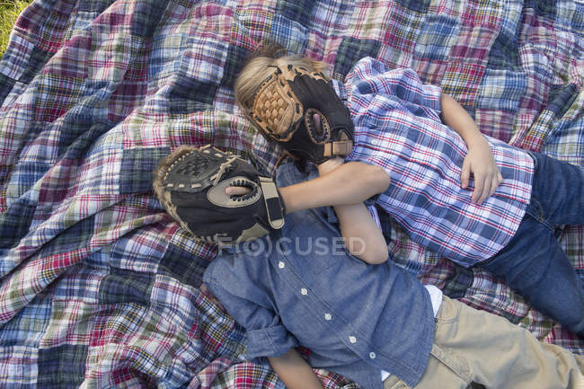Siblings covering face with baseball gloves while resting on blanket — Stock Photo