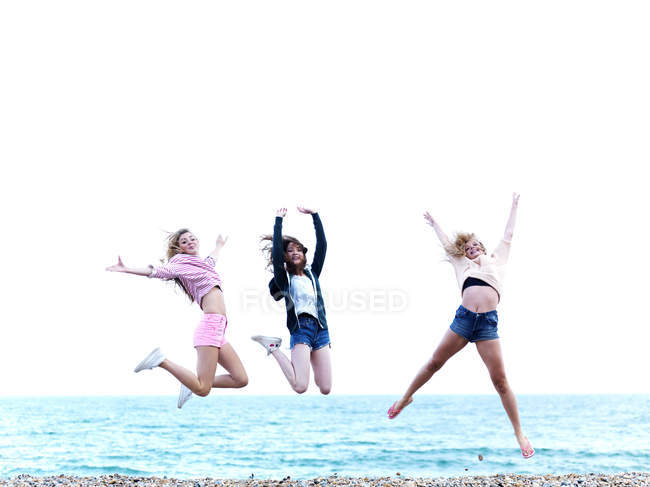 Three friends jumping in excitement on the beach — Stock Photo