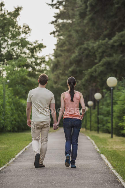 Rear view of young couple walking while holding hands in park — Stock Photo
