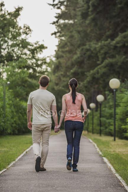 Vue arrière du jeune couple marchant tout en se tenant la main dans le parc — Photo de stock