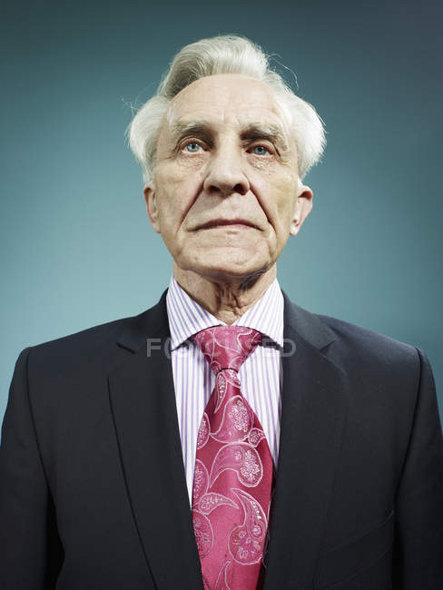 Portrait of elegant senior man wearing a suit and pink tie — Stock Photo