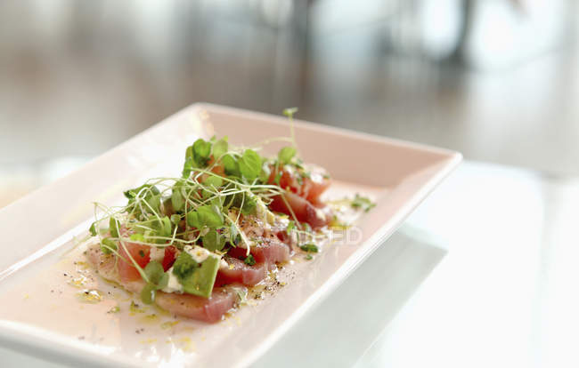 Close up view of plate of tuna sashimi with pea shoots on table — Stock Photo