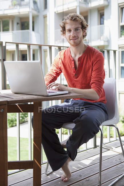 Portrait of young man using laptop at porch — Stock Photo