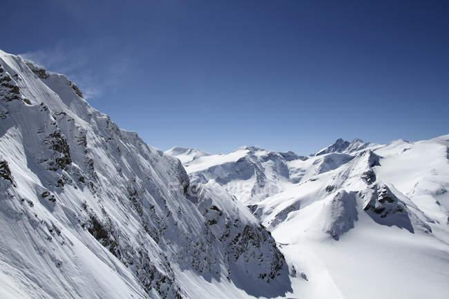 Vista panoramica del vento che soffia cime di montagna di neve contro il cielo blu — Foto stock
