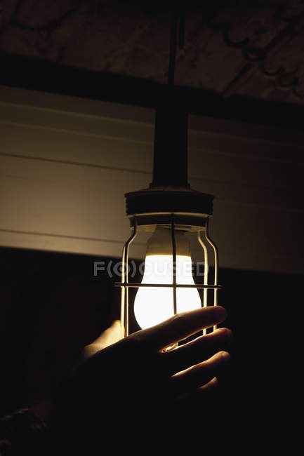 Crop male hand adjusting light bulb — Stock Photo