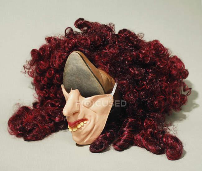 Composition artistique du visage en chaussure, masque et perruque sur fond gris — Photo de stock