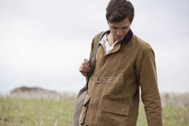Man wearing brown jacket carrying backpack in nature — Stock Photo