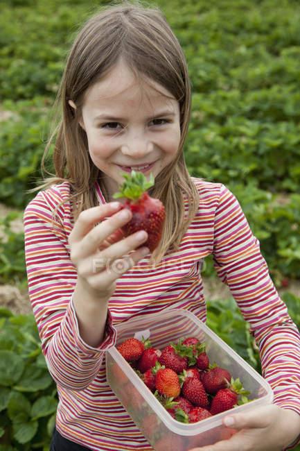 Ritratto di ragazza sorridente con scatola di fragole in mano — Foto stock